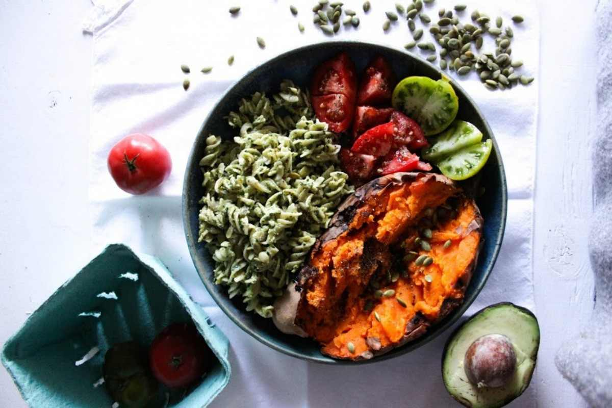 The-Glow-Bowl-Baked-Sweet-Potato-With-Pesto-Pasta-Tomatoes-and-Pumpkin-Seeds-1200x800