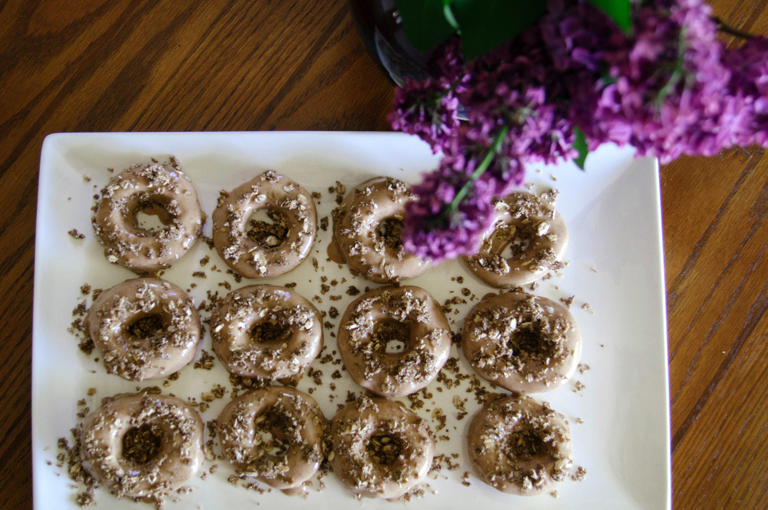Vegan Baked Coffee Doughnuts With Maple Glaze topped with nuts