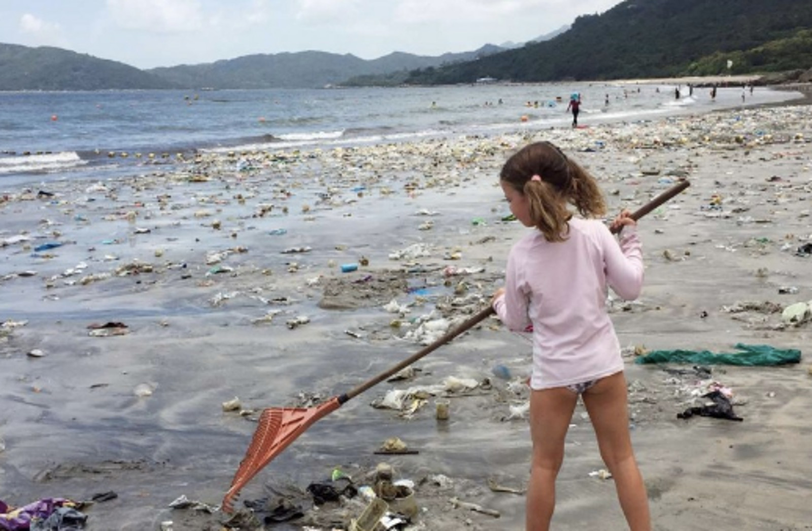 Photo of Little Girl Raking Up Plastic Trash on the Beach Foretells a Sad Future if We Don't Make a Change