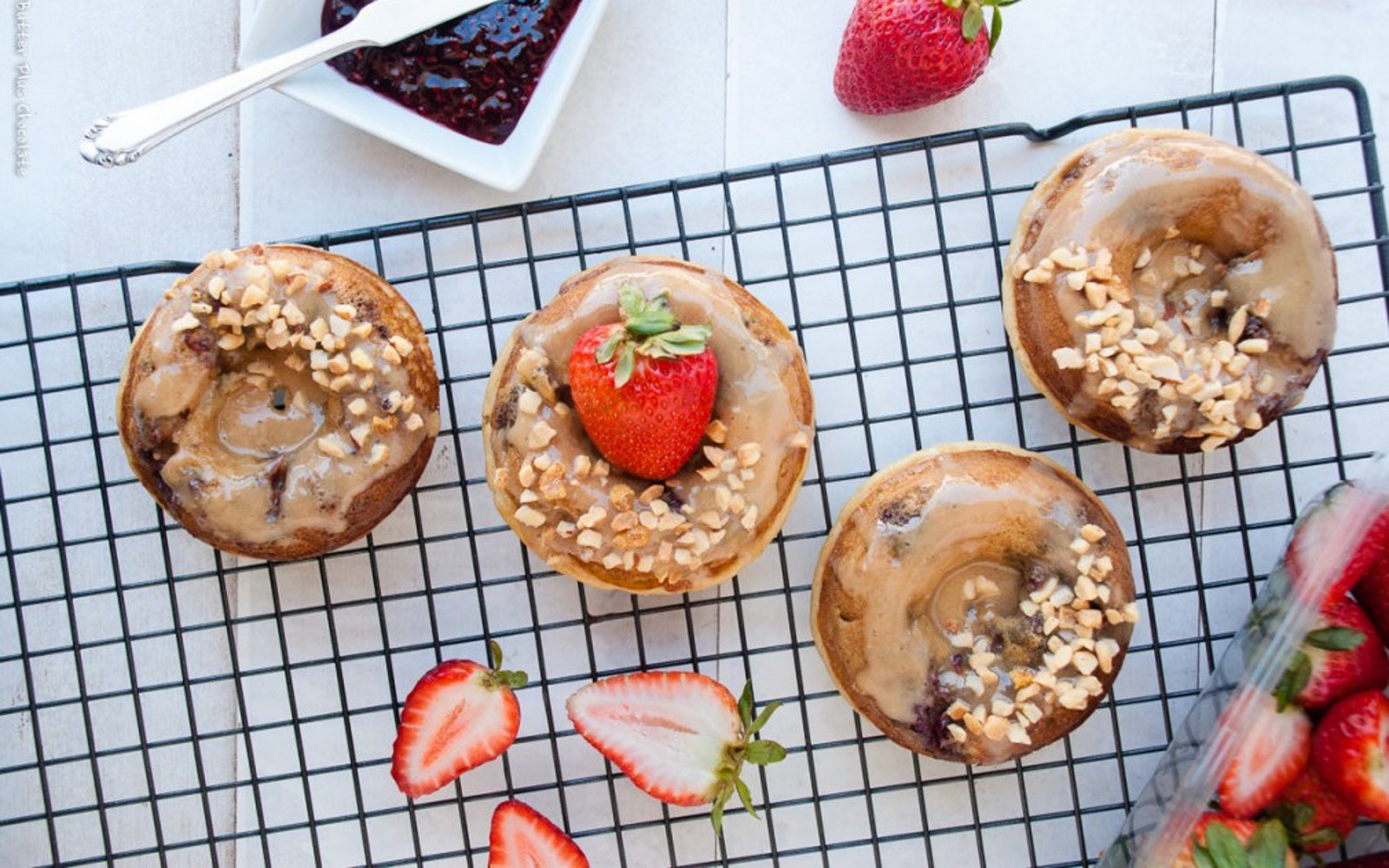 Vegan Healthier Peanut Butter and Jelly Baked Doughnuts with glaze, strawberries, and nuts to top