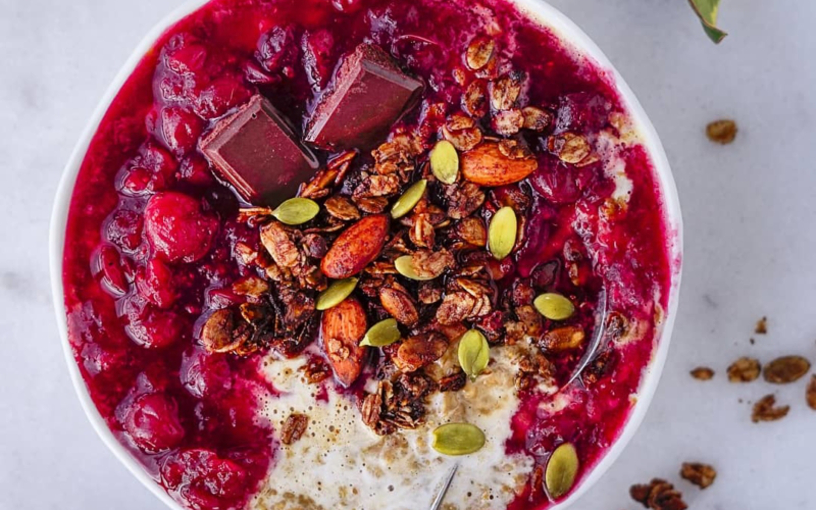 Vegan Gluten-Free Gingerbread Oatmeal with Warm Cranberry Orange Sauce topped with seeds and chocolate