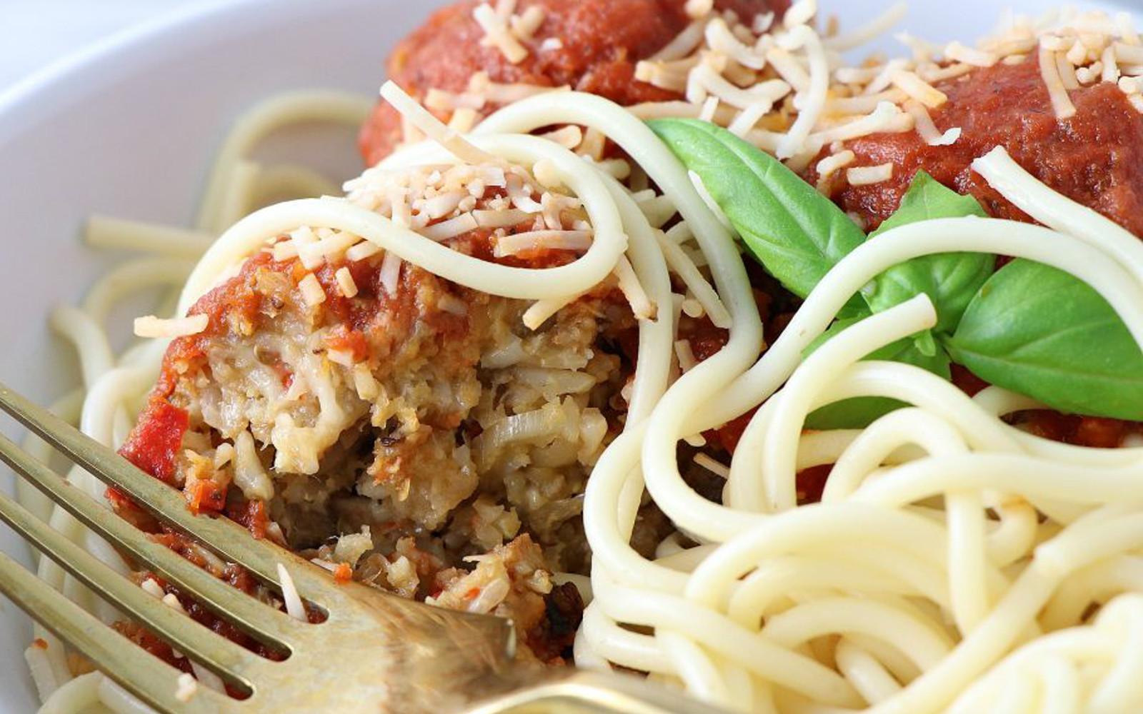 Vegan Eggplant Cauliflower Meatballs over pasta with sauce and vegan cheese cut open