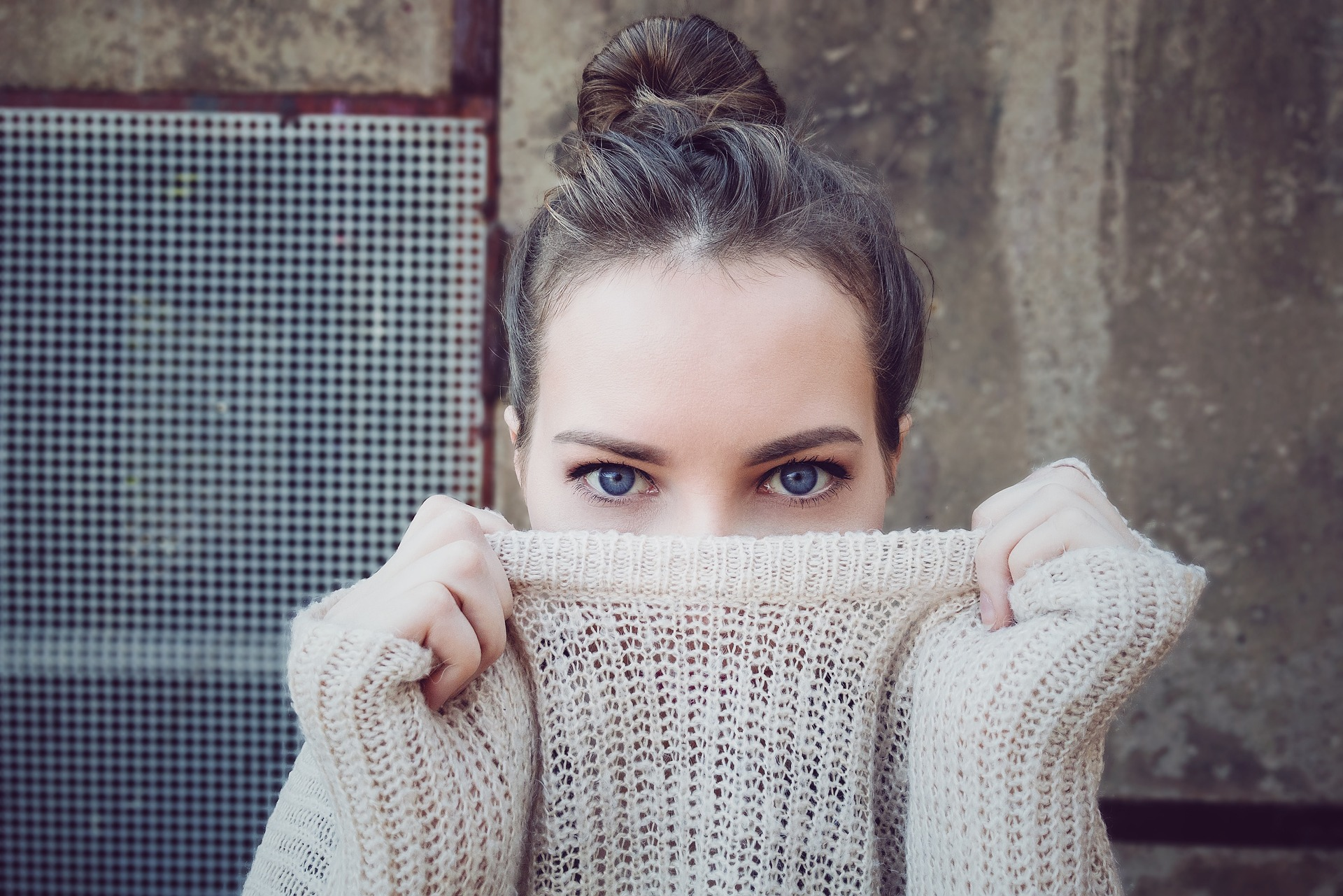 Girl with sweater over her mouth