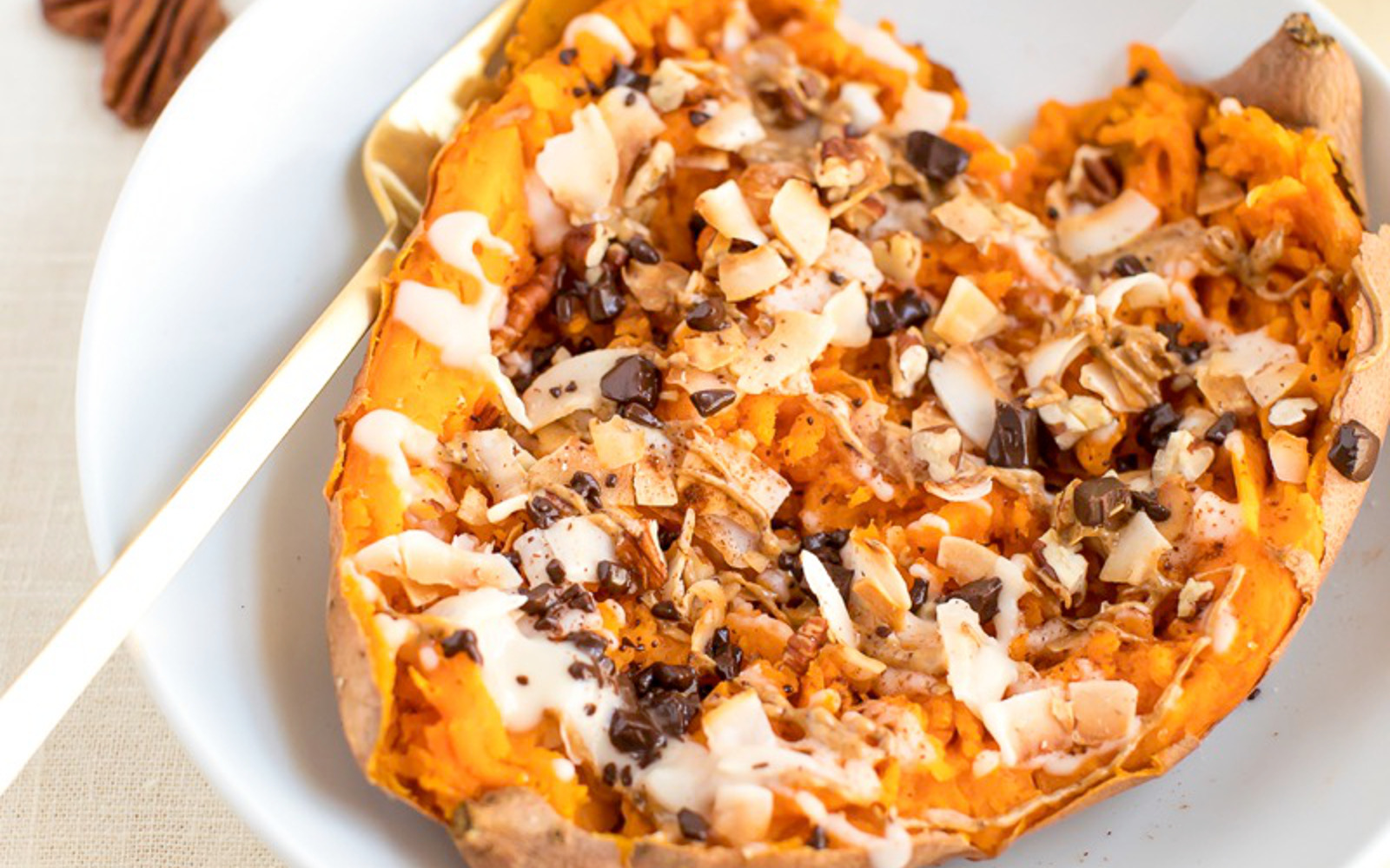 Vegan Healthy Dessert Baked Sweet Potato topped with almond flakes, coconut, dark chocolate, cinnamon, and pecans