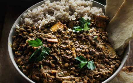 Vegan GLuten-Free Curried Green Lentil Dal with Sweet Potatoes and Mushrooms topped with garnish and side of rice