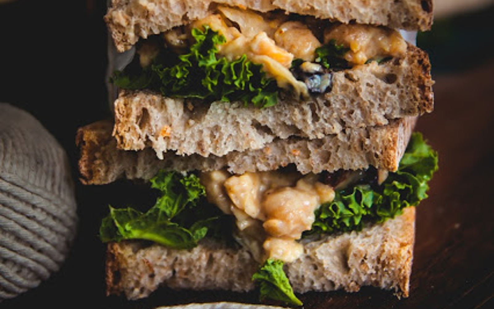 Vegan Coronation Chickpea Sandwiches between sourdough with greens