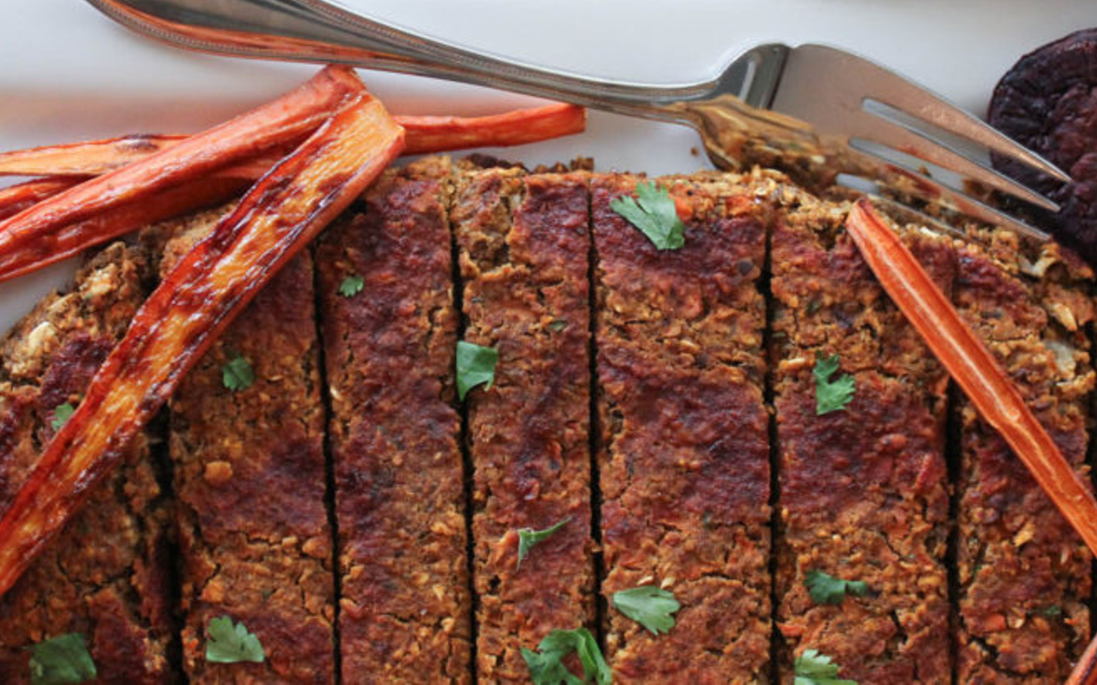 Vegan Gluten-Free Lentil Vegetable Loaf after baking topped with herbs and roasted carrots