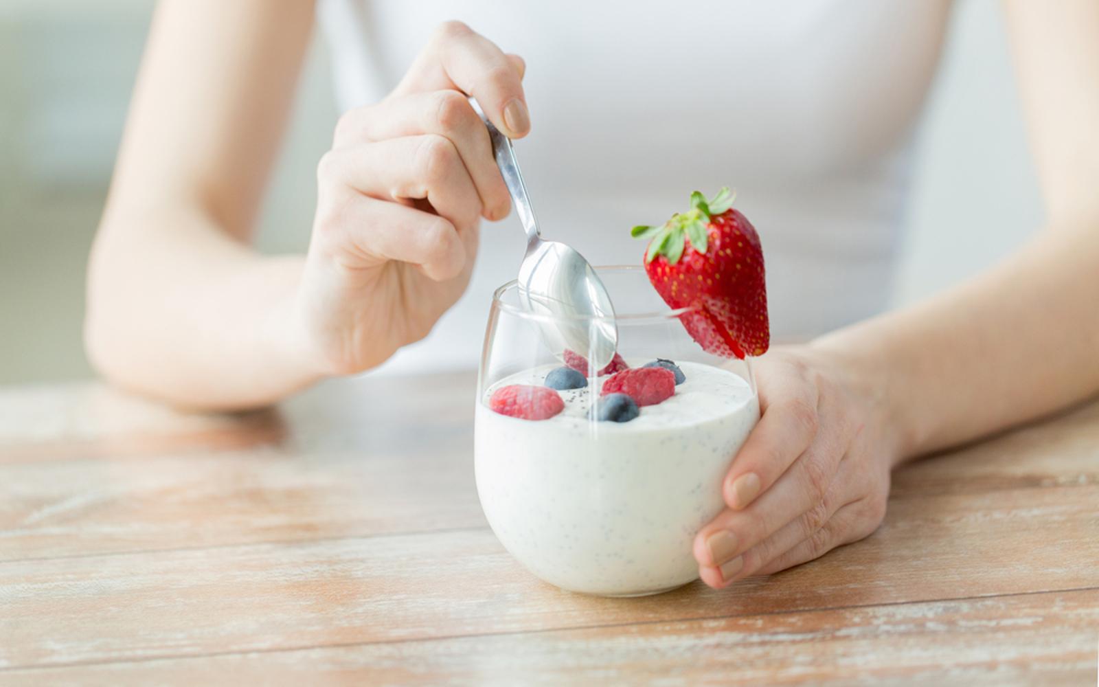 Woman with vegan yogurt and fresh strawberries