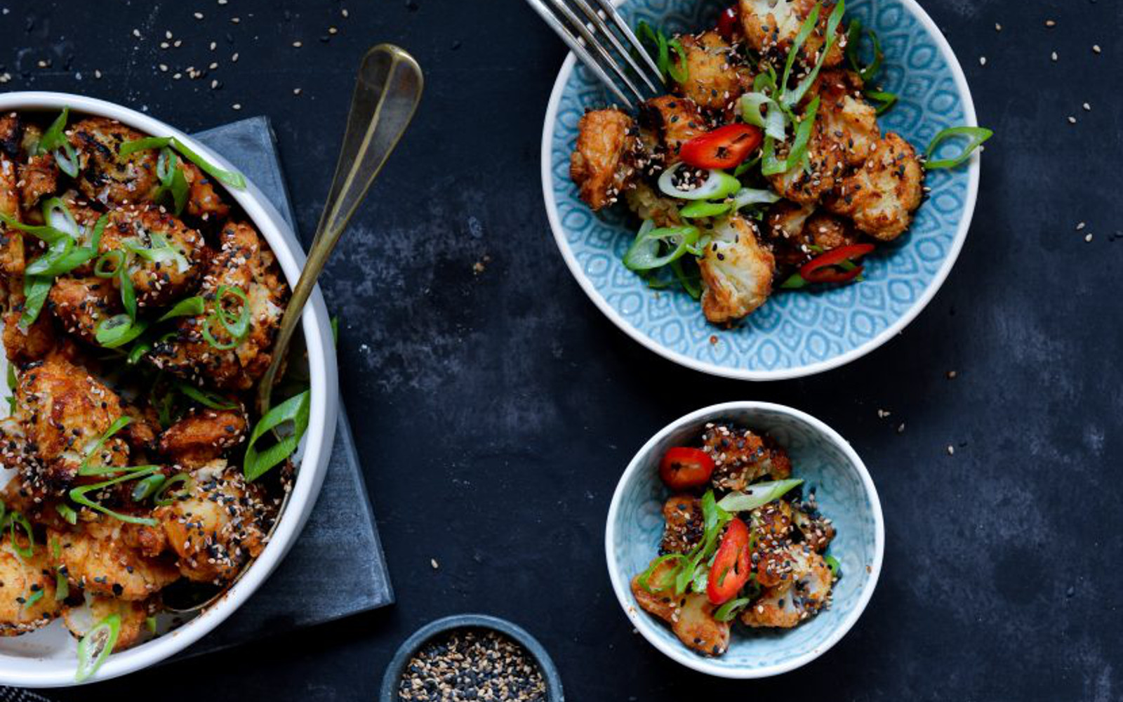 Vegan Gluten-Free Sticky Spicy Cauliflower Topped with sesame seeds, green onion, and red peppers