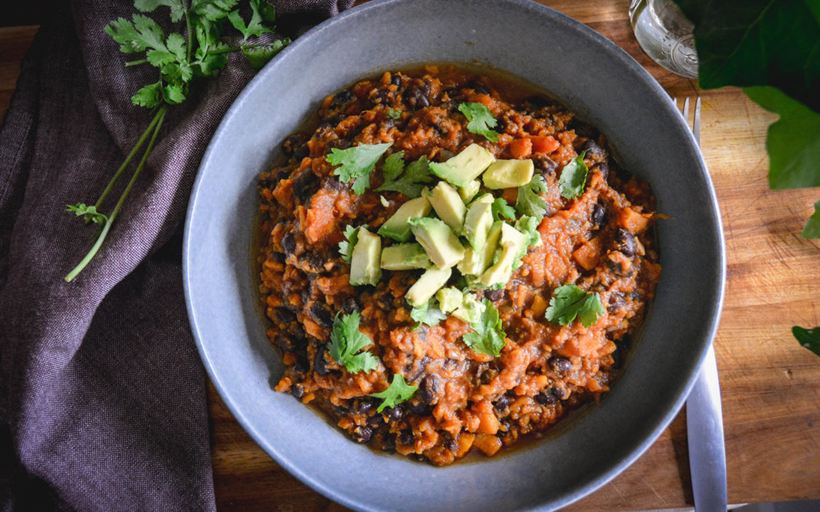 Vegan Gluten-Free Sweet Potato Chili topped with herbs and avocado