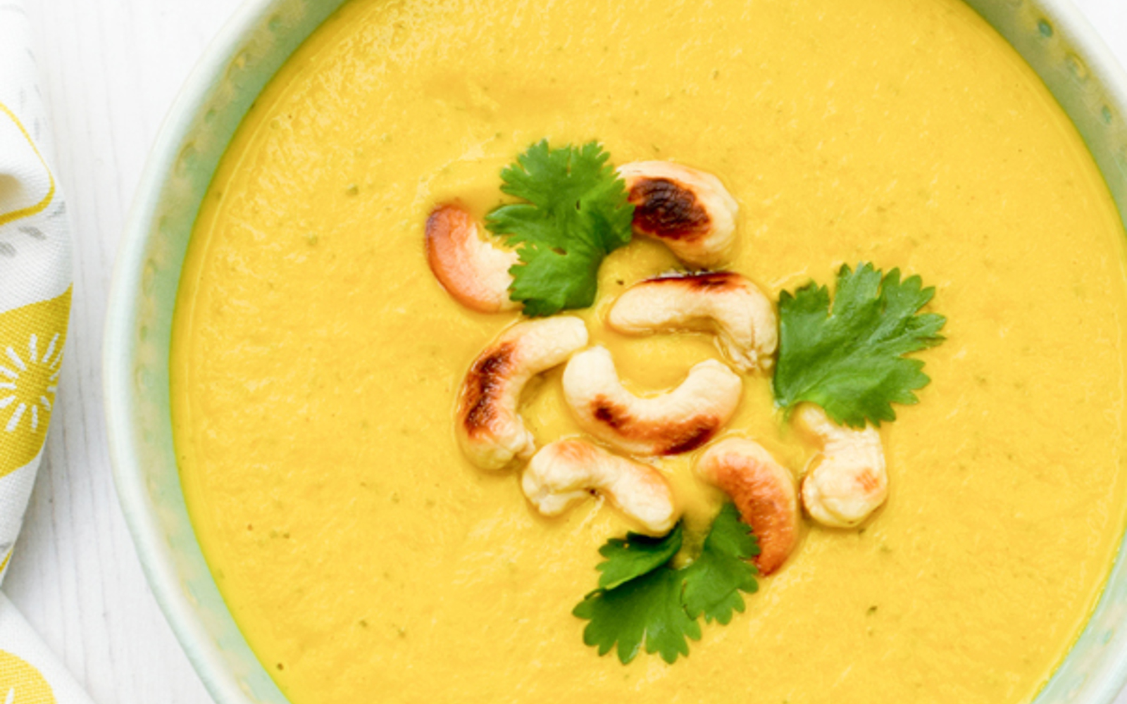 Carrot and Cashew Soup Vegan Gluten-Free with whole cashews and herbs to garnish