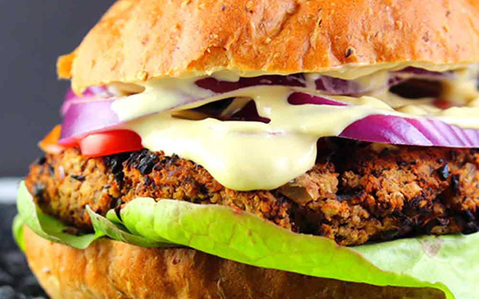 Vegan Red Bean and Mushroom Cheeseburgers with melted cheese sauce and red onion