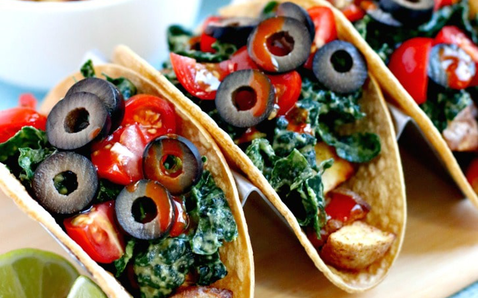 Vegan Gluten-Free Potato Tacos with Massaged Kale with olives and hot sauce