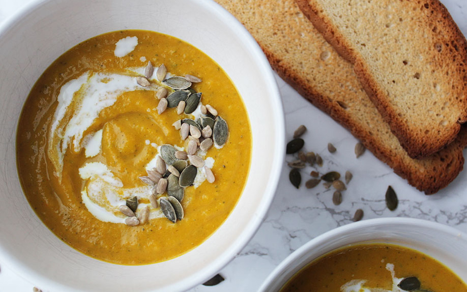 Vegan Gluten-Free Curried Coconut and Butternut Squash Soup with cream and pumpkin seeds
