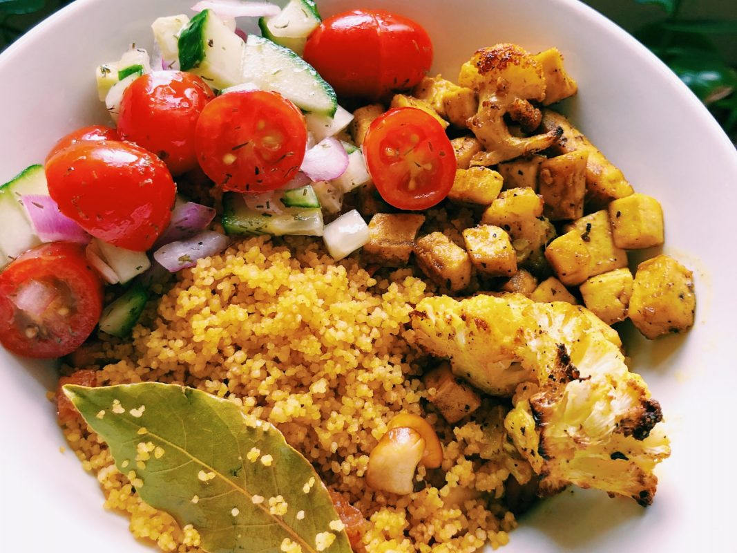 golden couscous bowl with tomato salad