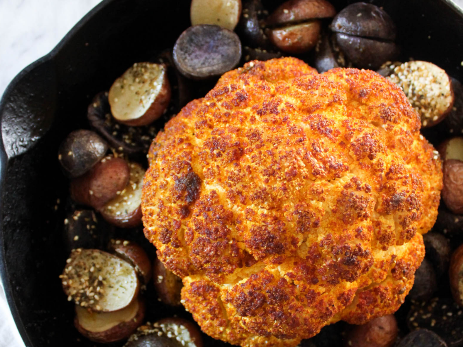Whole roasted cauliflower with potatoes in cast iron pan