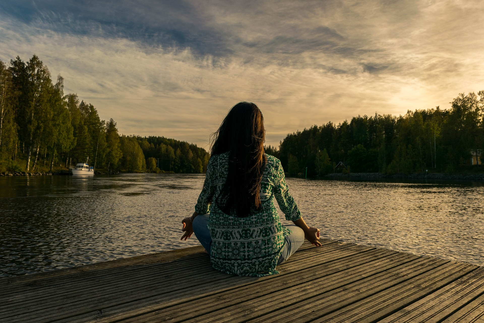Woman meditating on a pier