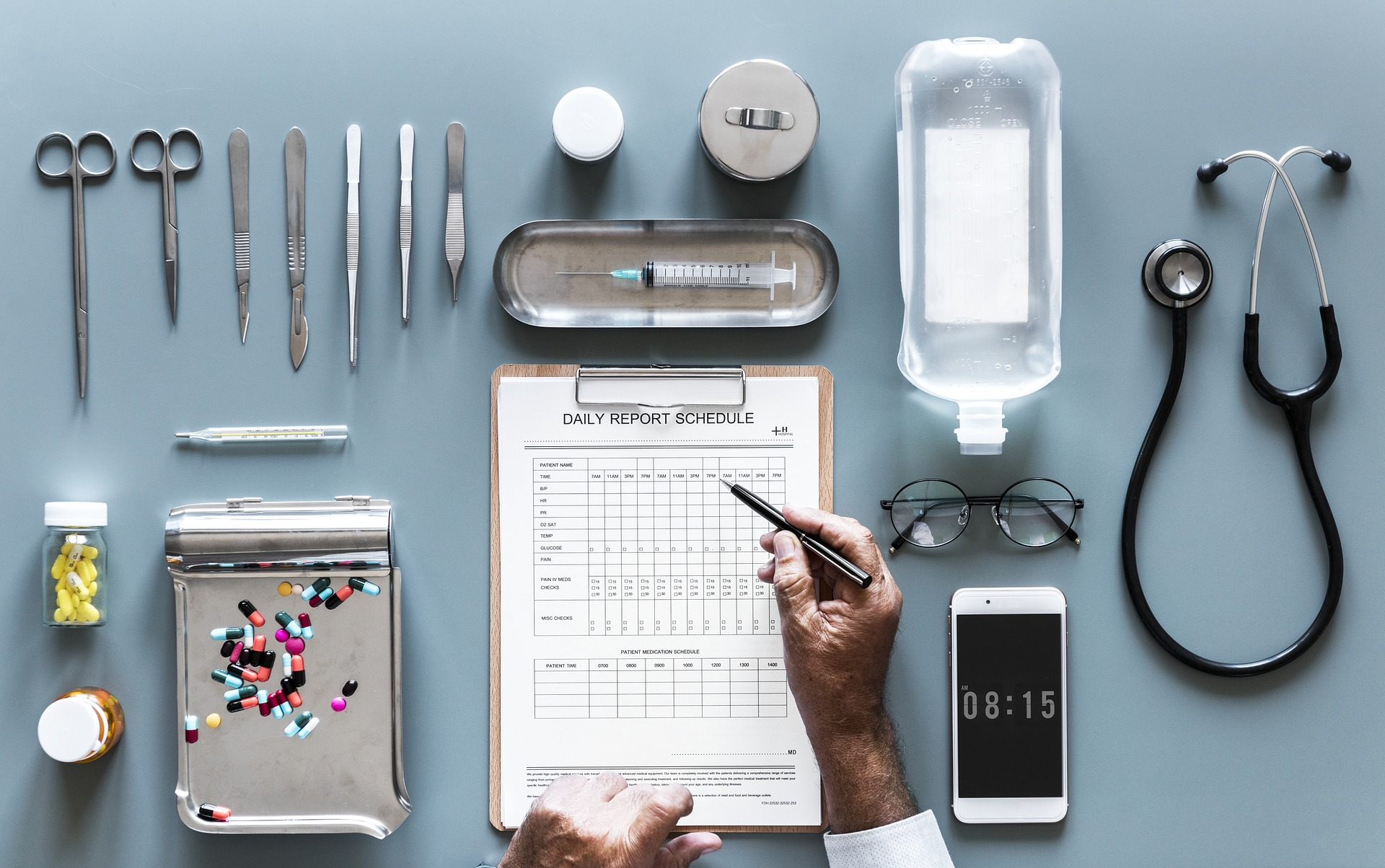 Doctor's hands filling out a chart with medical tools on a table