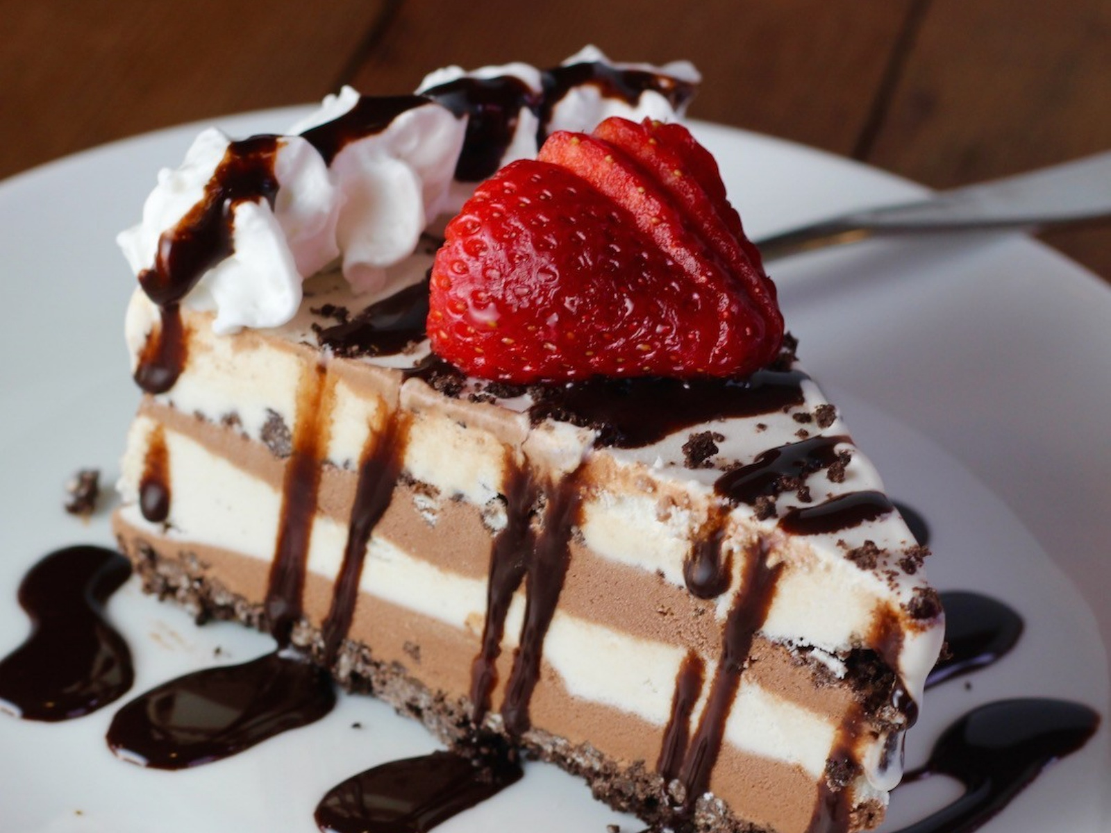 Ice Cream Caketopped with strawberries and drizzled with chocolate