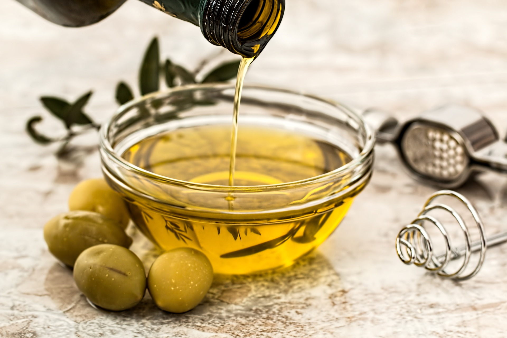 olive oil in a glass next to olives