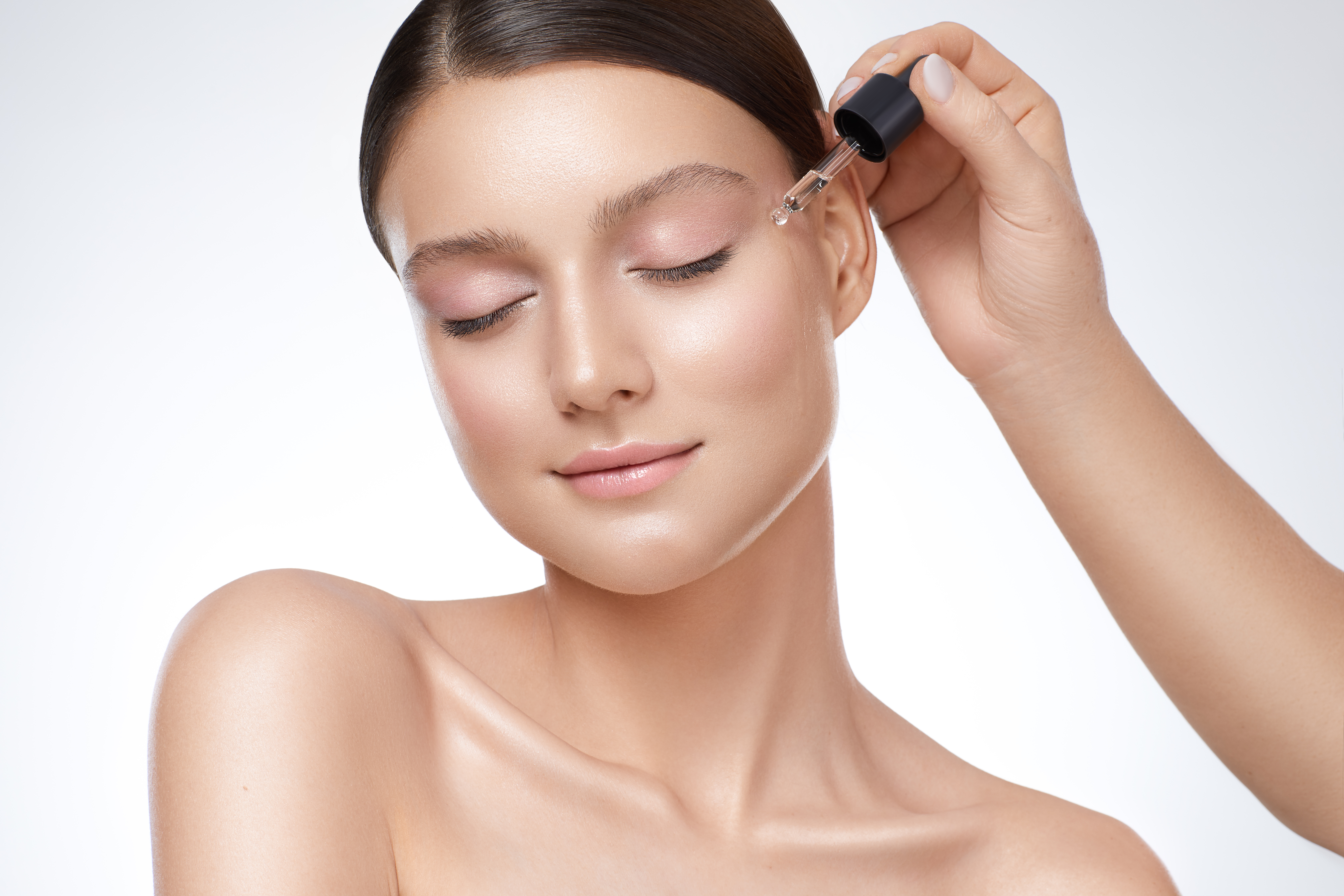 Woman applying hyaluronic acid serum to her face