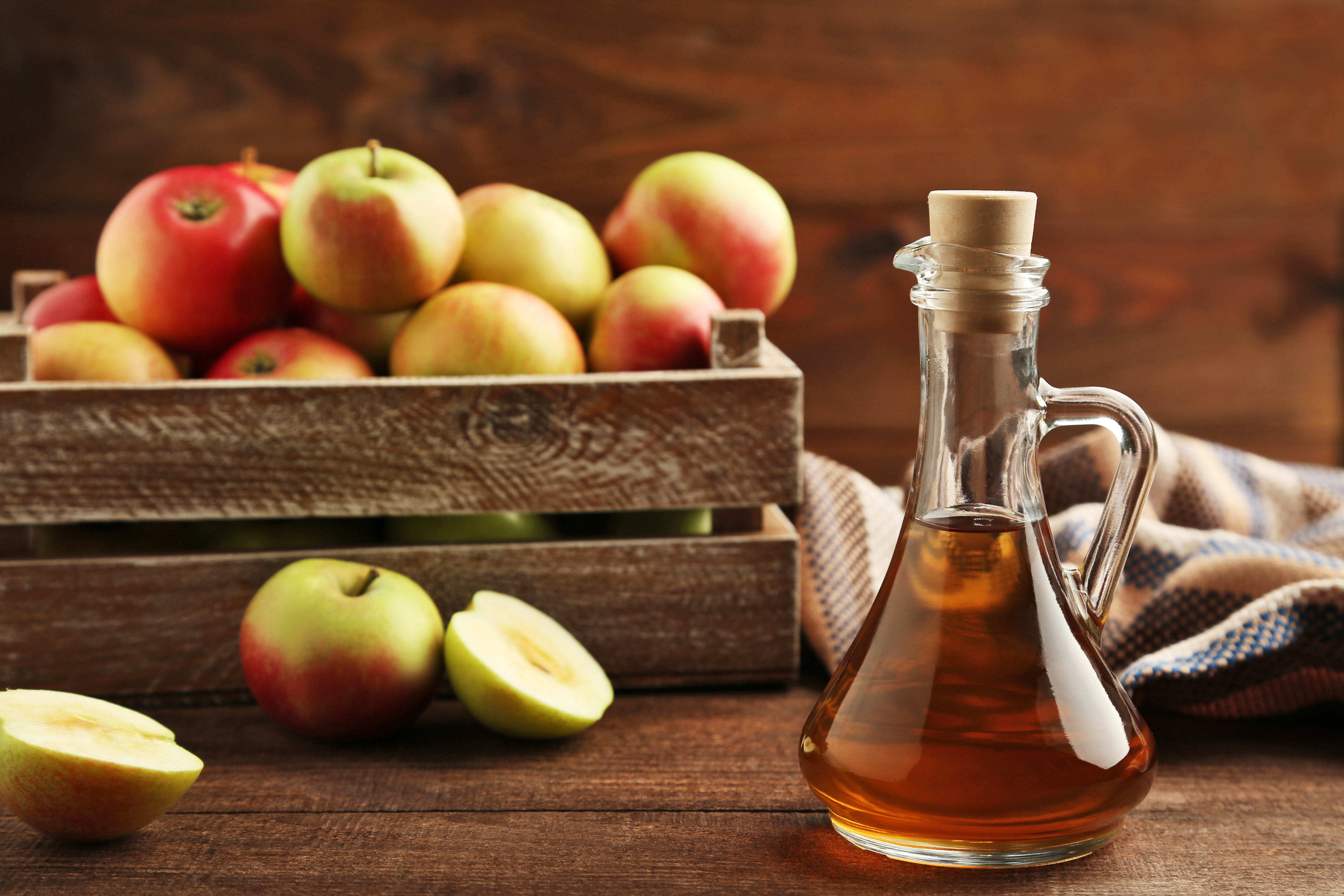 Apple cider vinegar in front of a basket of apples