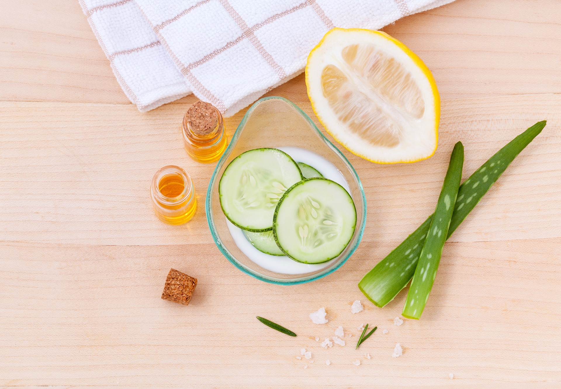 Cucumber, aloe vera, and lemon on a table with a towel