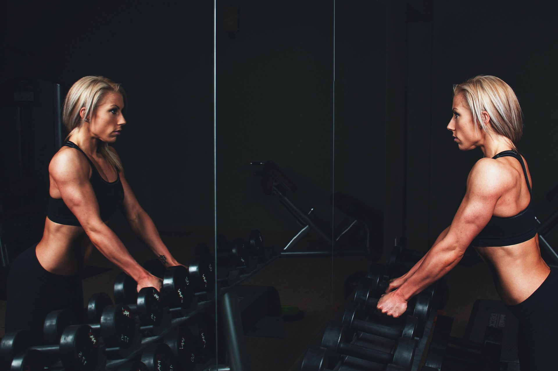 Woman holding weights looking in the mirror