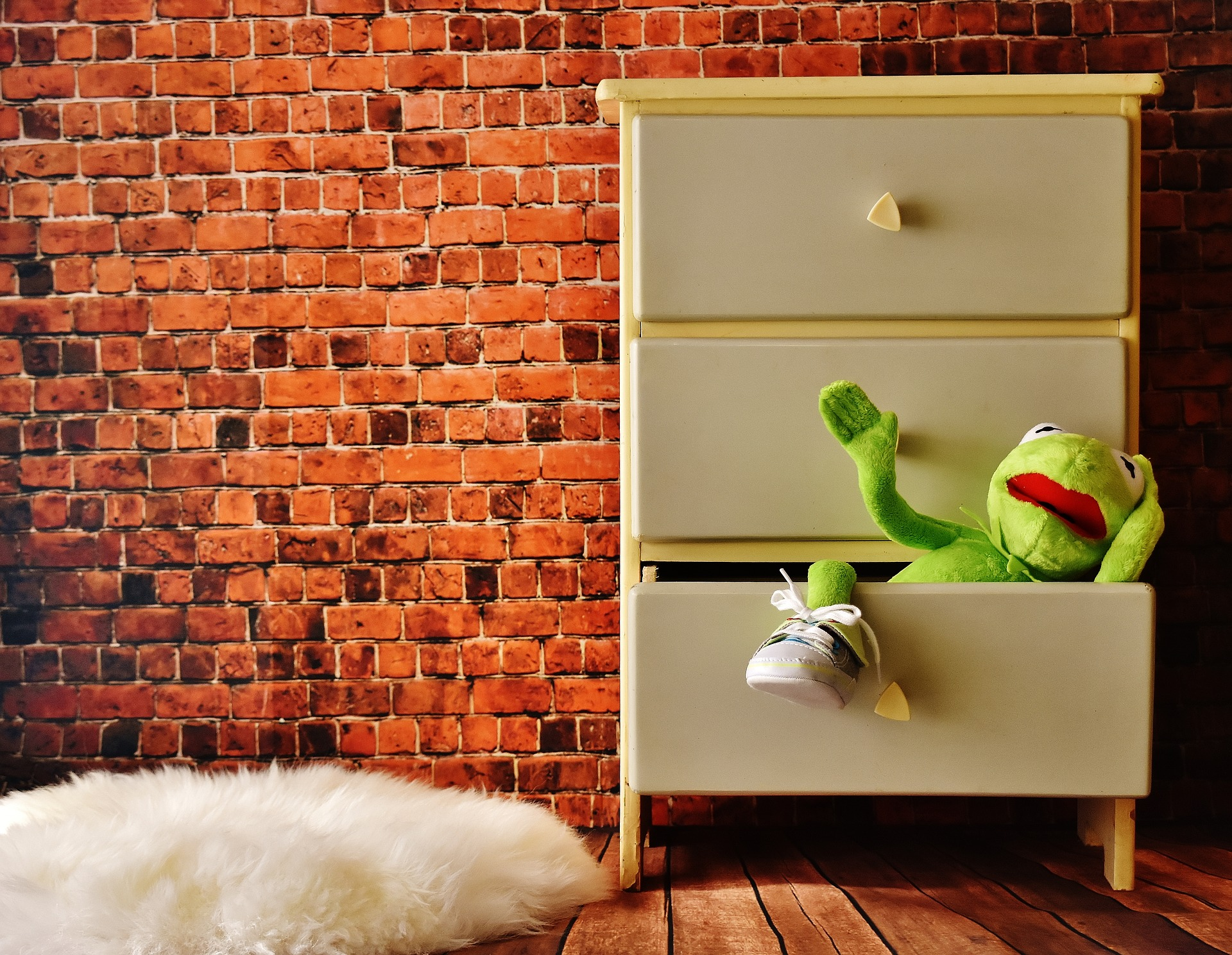 Drawer with stuffed kermit toy hanging out