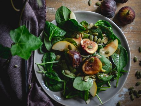 Spinach and fig salad tossed with pumpkin seeds