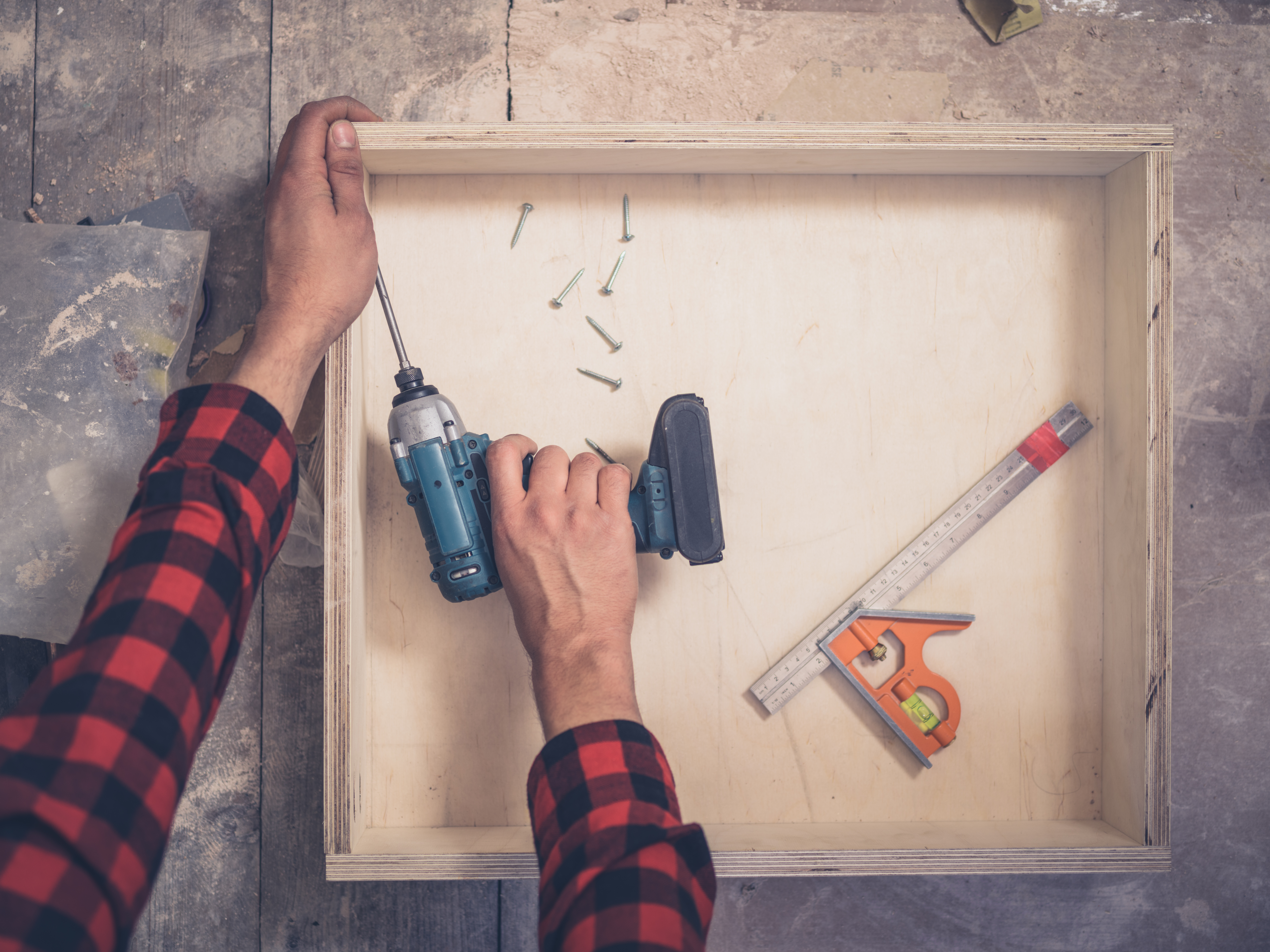 Man holding tools over a drawer
