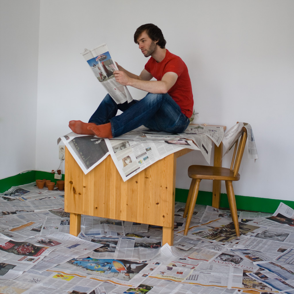 Man sitting on newspapers and reading a newspaper