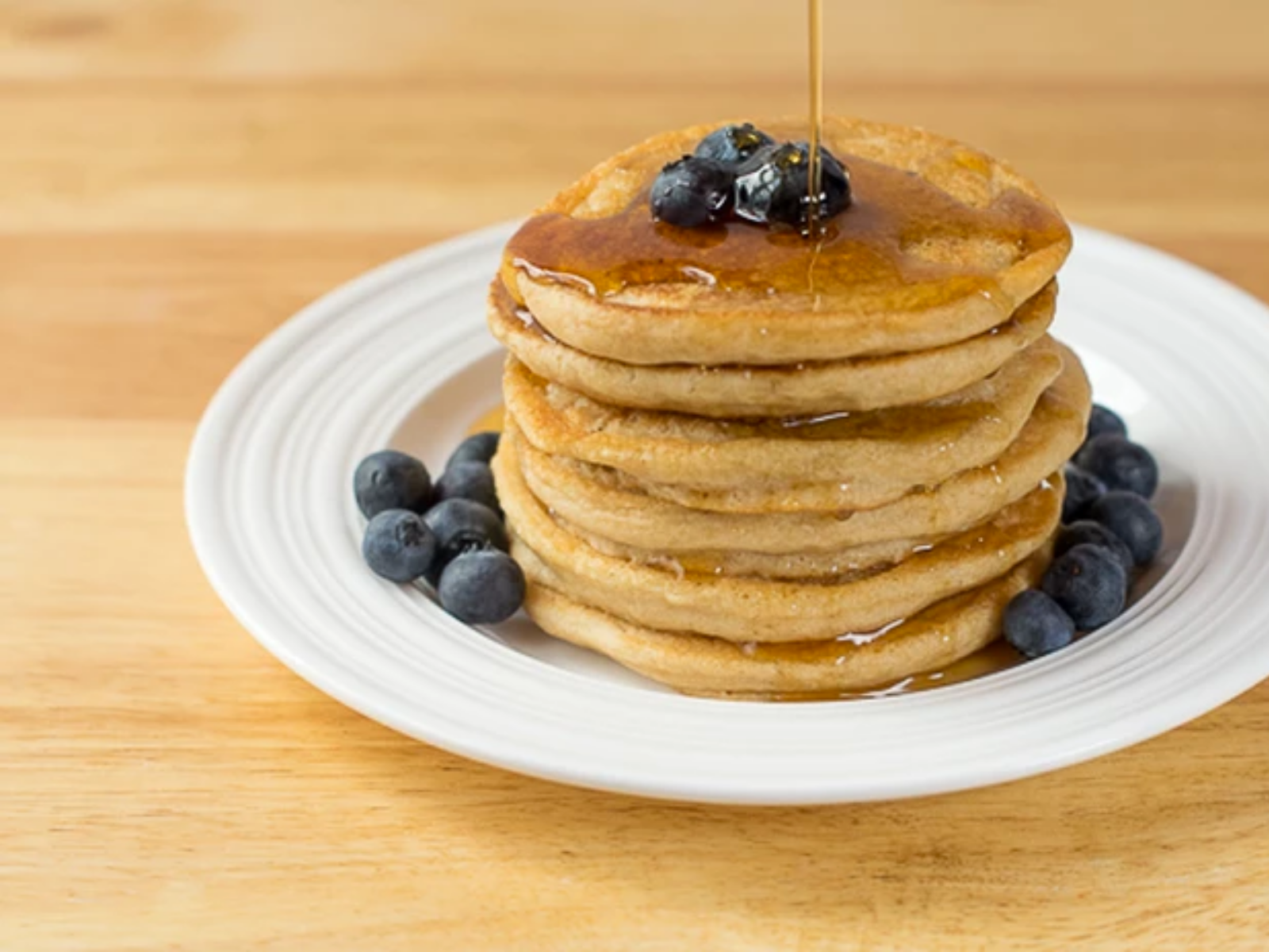 Fluffy vegan pancakes with blueberries and maple syrup
