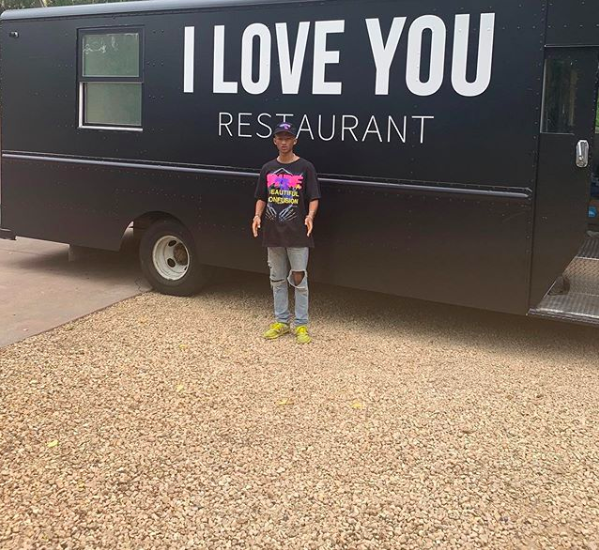Jaden Smith in front of his I Love You vegan food truck for the homeless