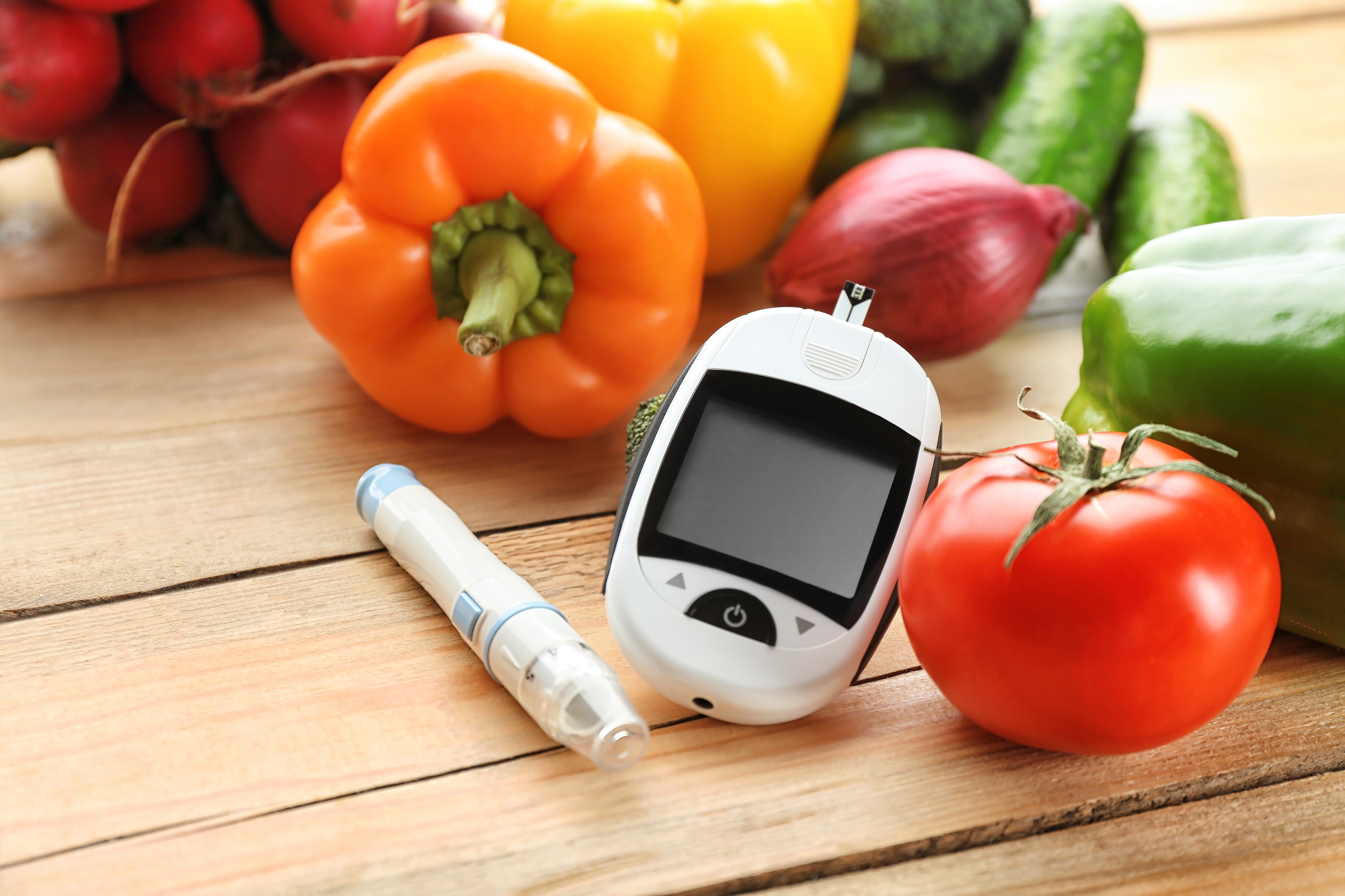 diabetes monitor on table with vegetables