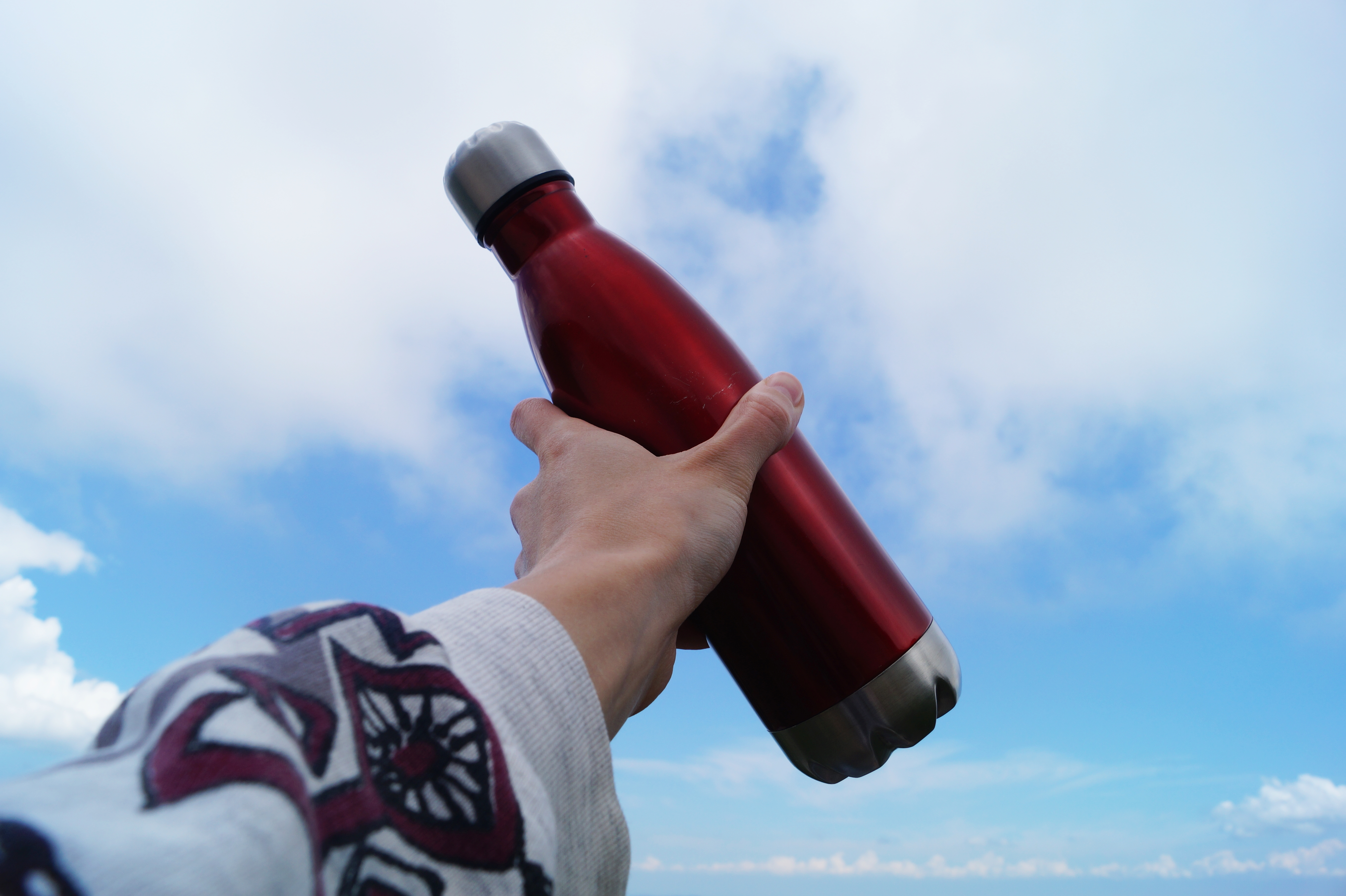 hand holding red stainless steel reusable water bottle