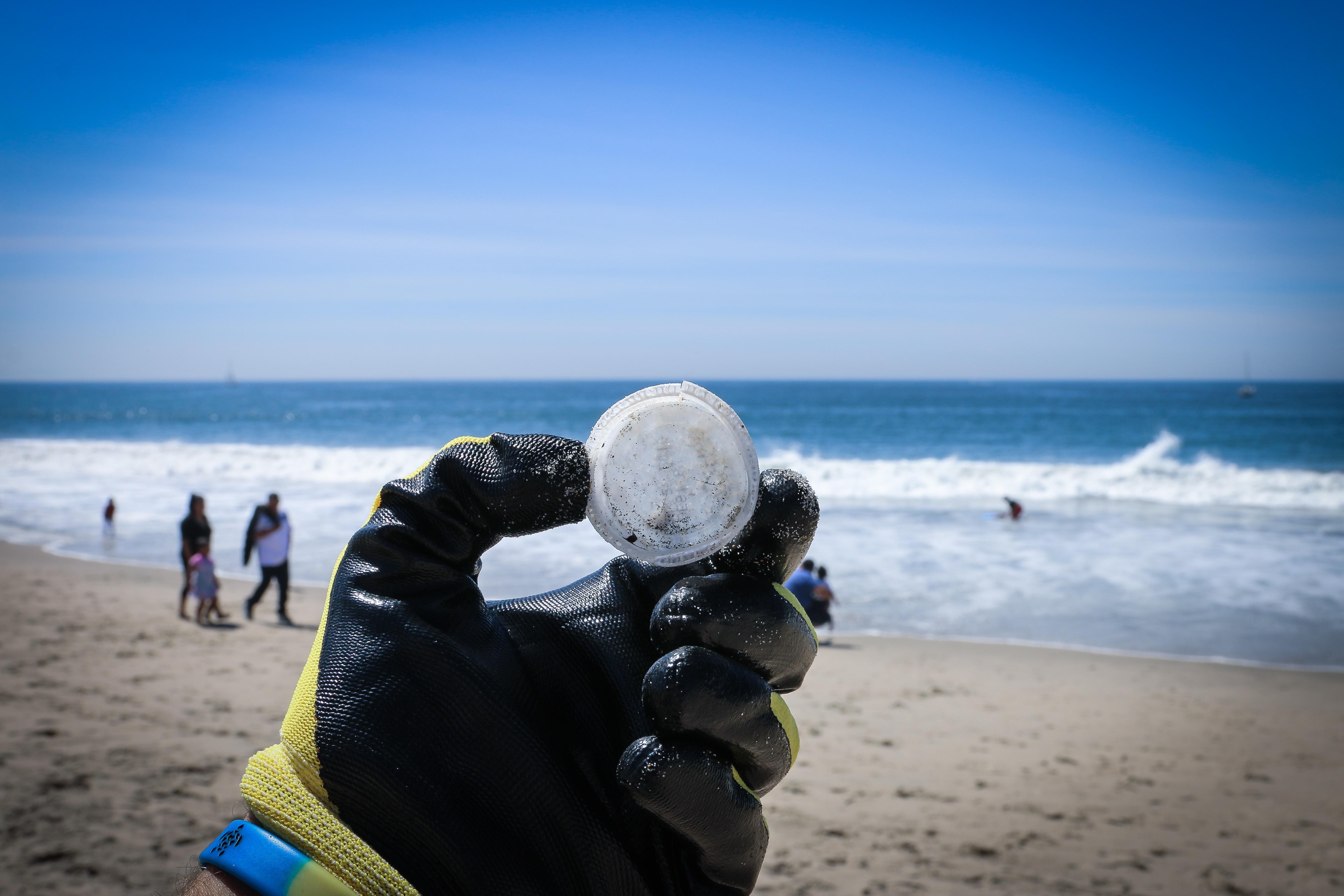 Plastic Cap in Hand on Beach