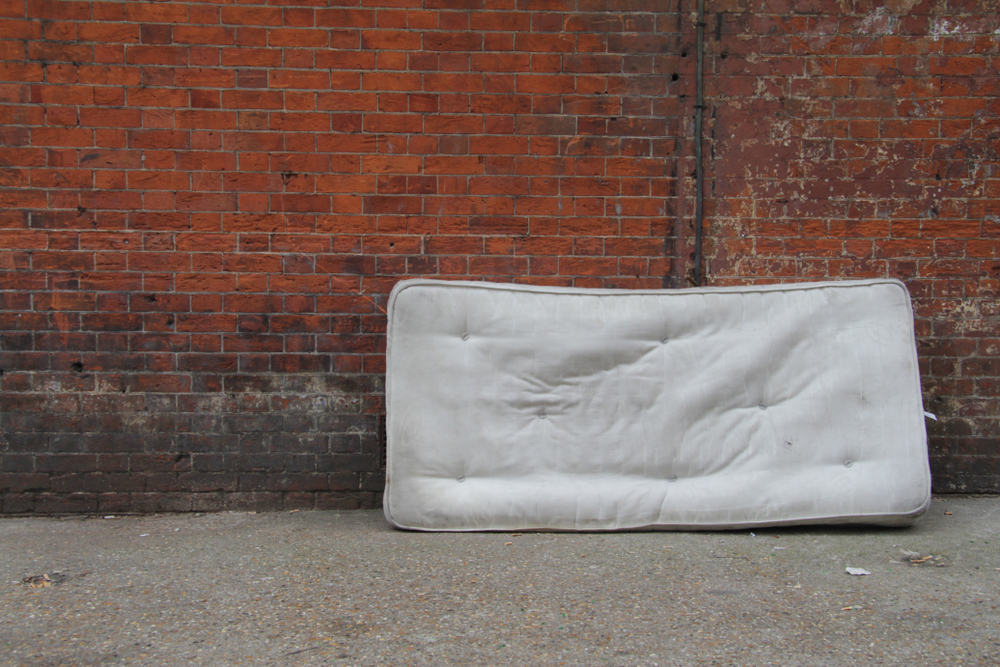 old mattress against a brick red wall