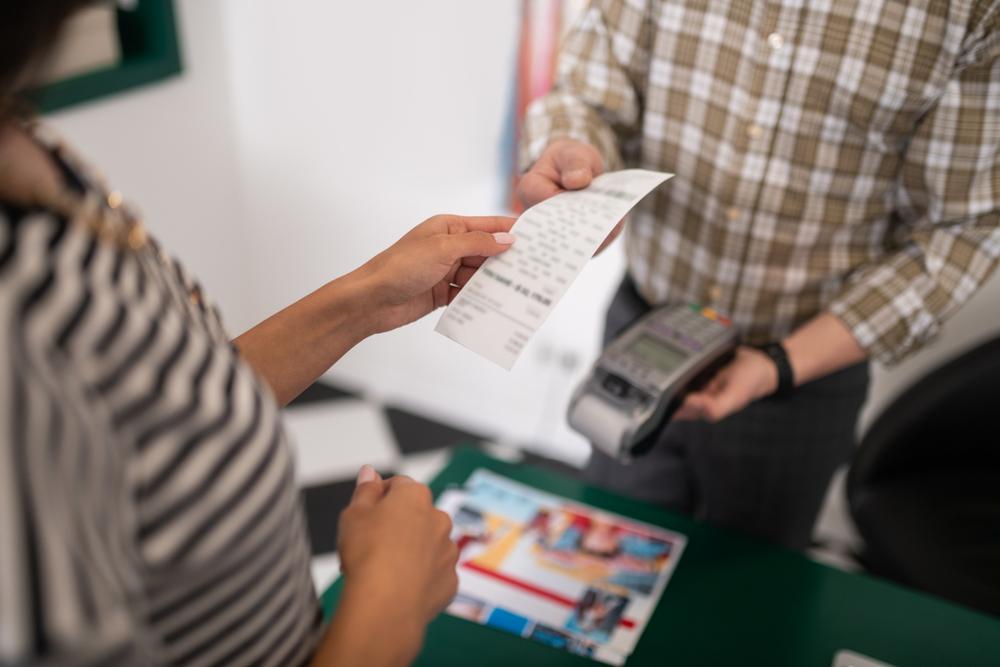 cashier handing receipt to customer