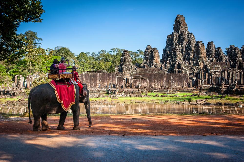 People riding an elephant at Angkor Wat
