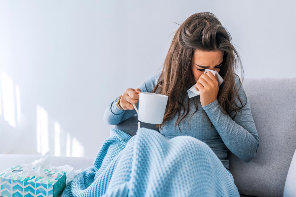 Woman with tea and blanket suffering from winter indoor allergies