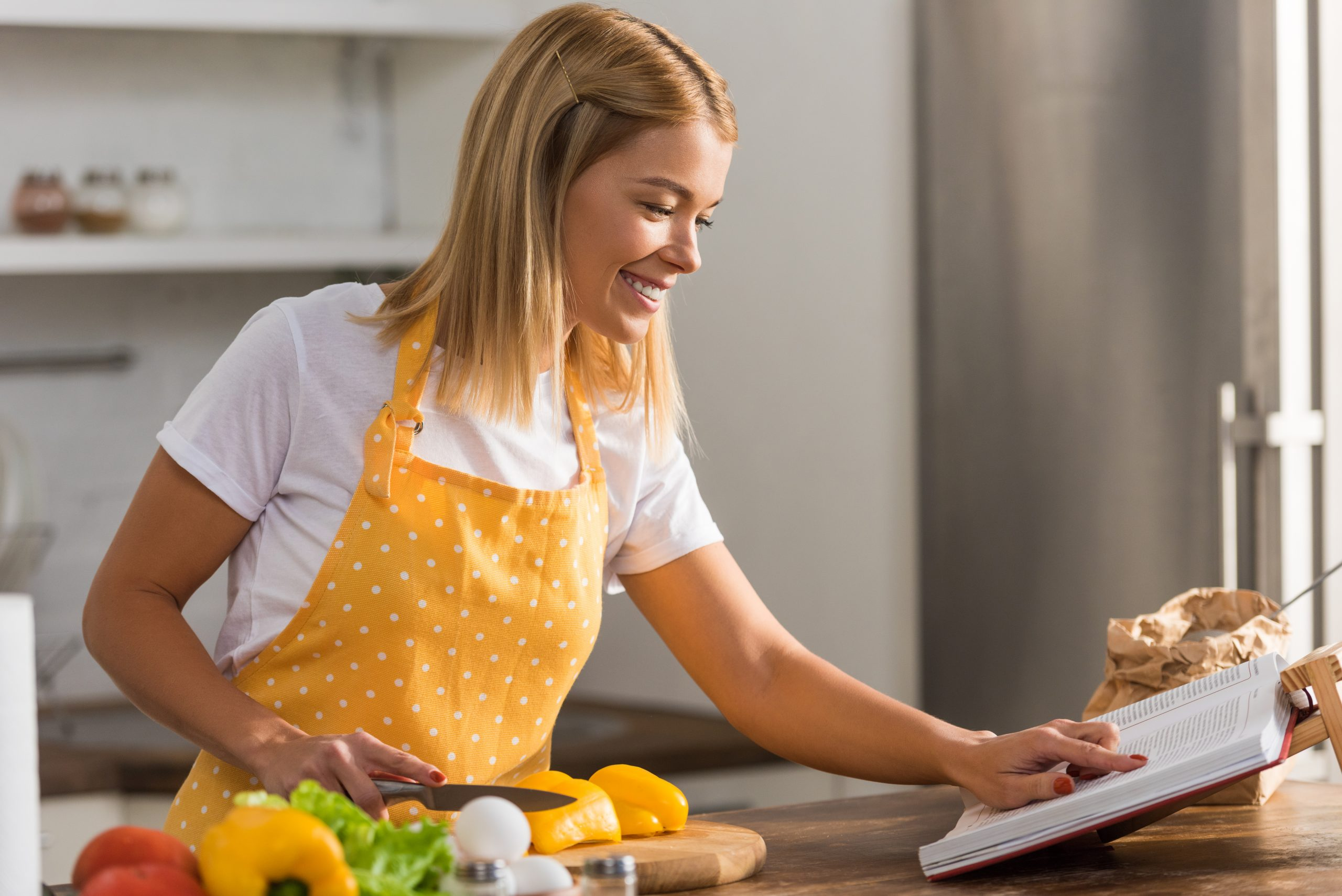 young woman in apron reading a cookbook