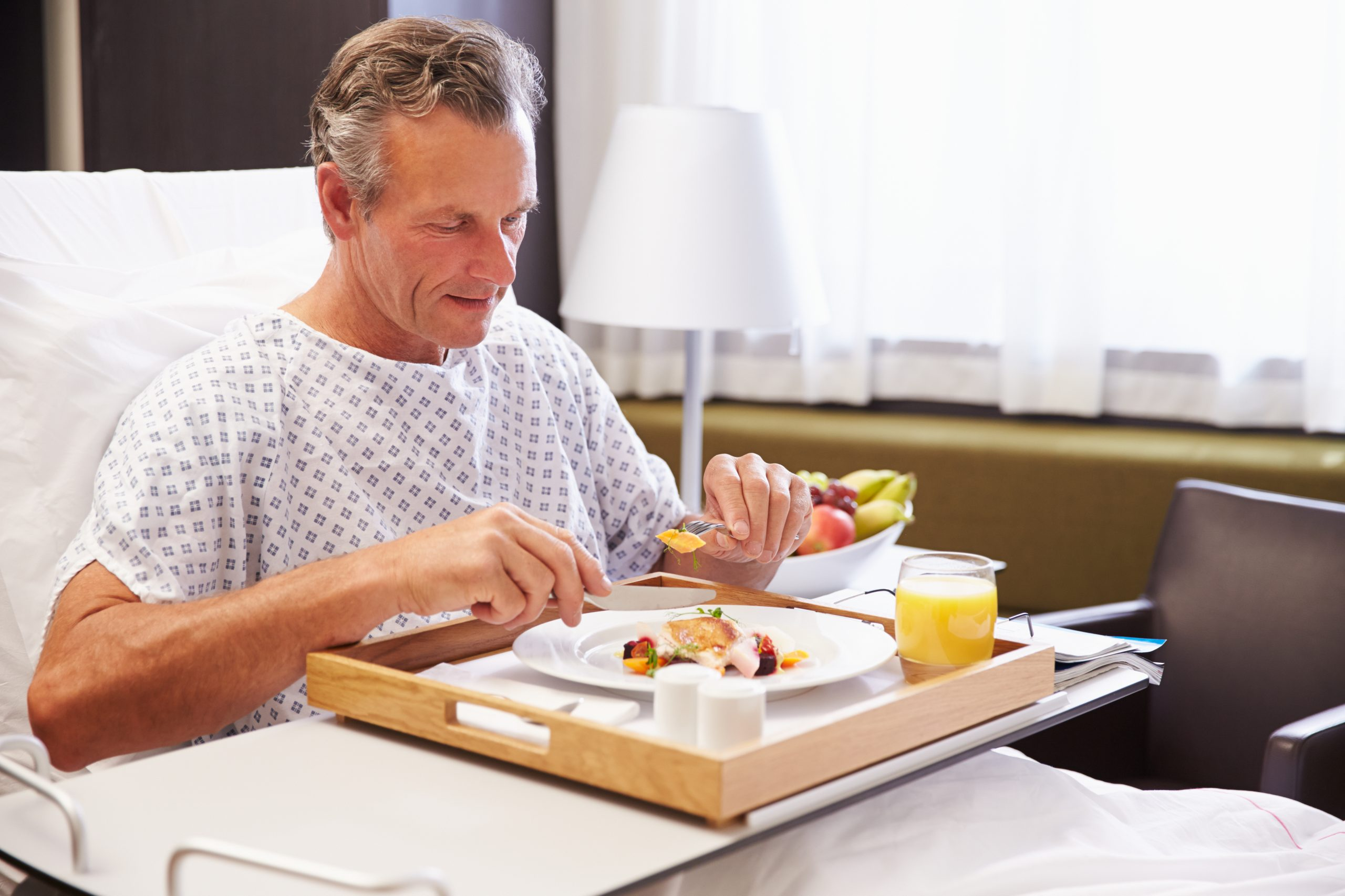 Man in Hospital Bed Eating