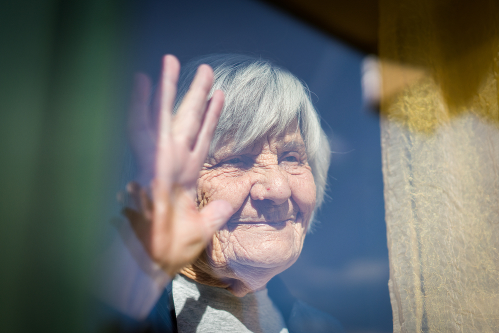 senior citizen waving on window