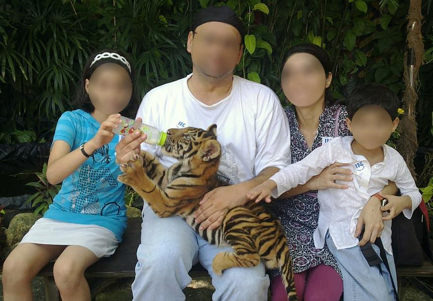 Family engaging in cub petting.
