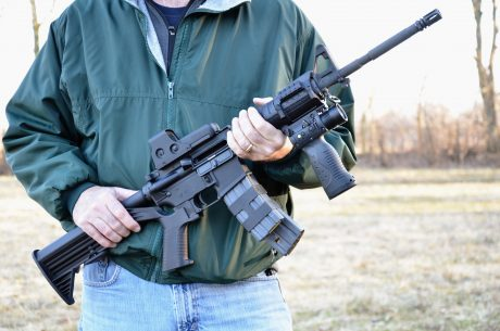 man holding assault rifle