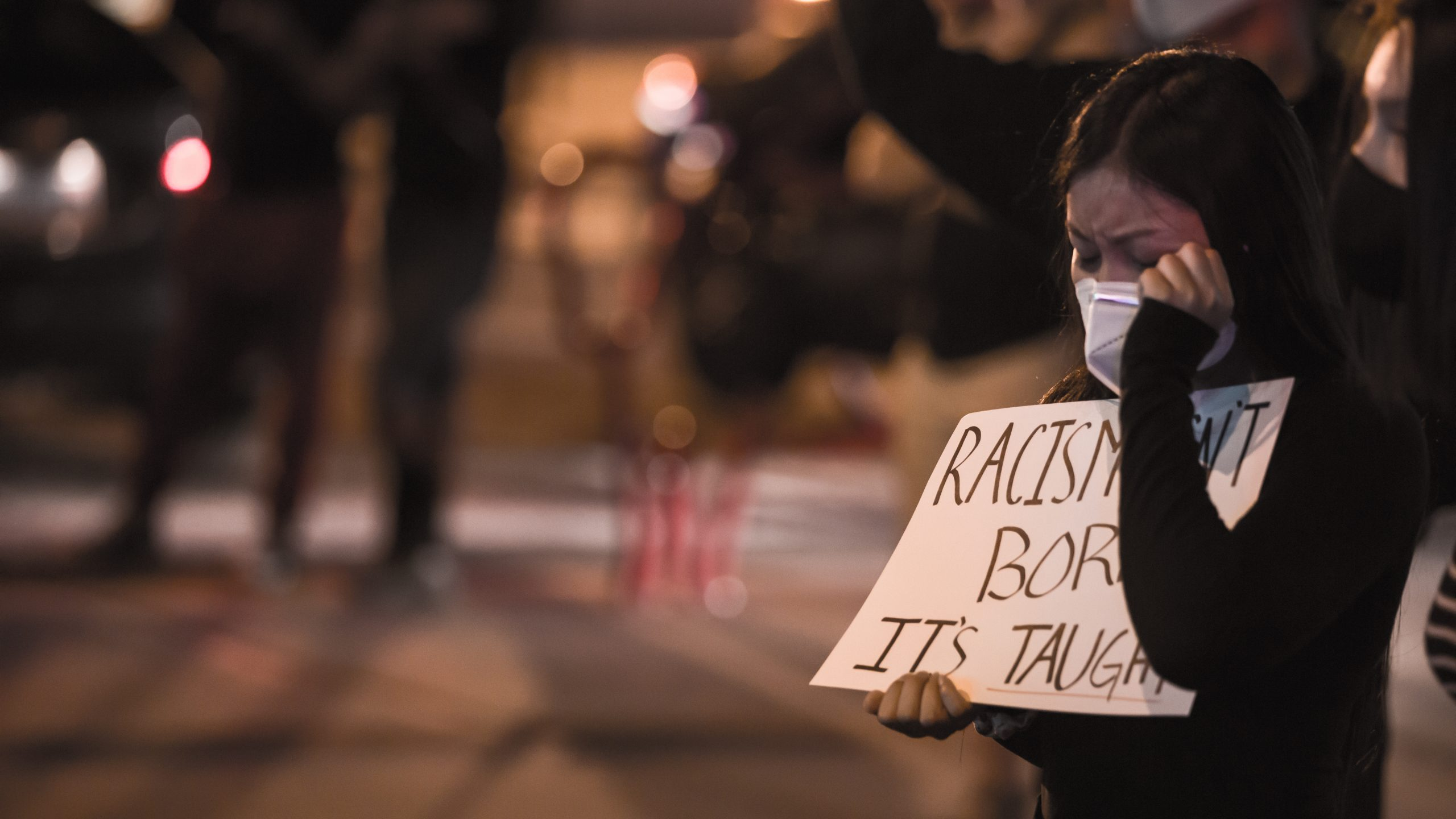 """Las Vegas, NV, USA 5/30/2020 — An Asian woman wipes her tears holding a sign that reads, """"Racism isn't born. It's taught."""" Black Lives Matter protest in Downtown Las Vegas."""