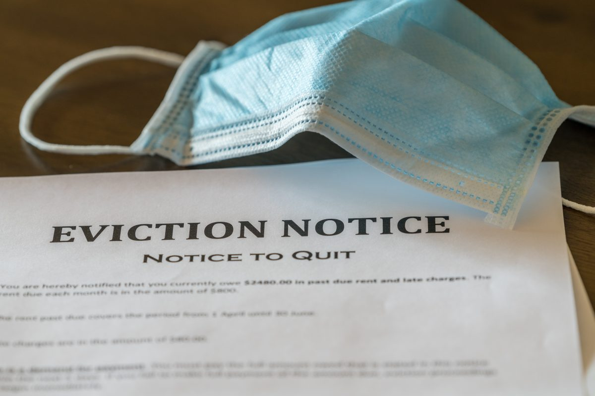 Face mask above eviction notice on table.