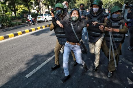 Woman wearing mask being arrested at a protest in India.