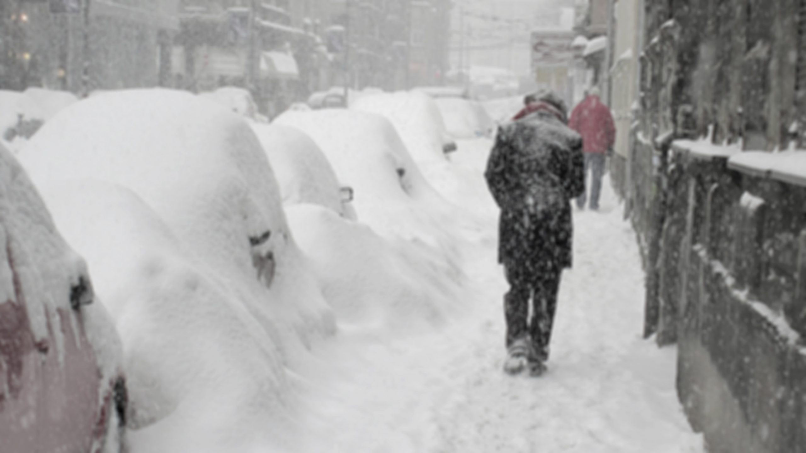 Man walking by snow-covered cars in snowstorm.